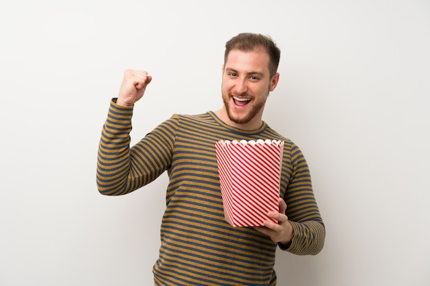 Handsome man over isolated white wall holding a bowl of popcorns Premium Photo