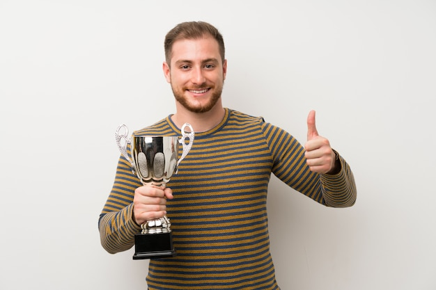Handsome man over isolated white wall holding a trophy Premium Photo
