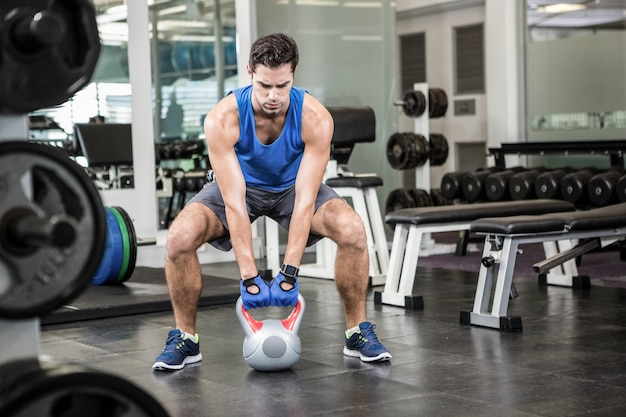 Handsome man lifting kettlebell at the gym Premium Photo