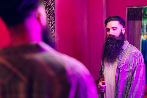 Красивый мужчина, глядя на себя в зеркало в новой рубашке Бесплатные Фотографии
