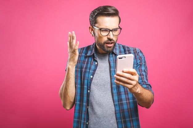 Красивый мужчина выглядит шокирован в смартфоне. люди, эмоции и технологии концепция. Premium Фотографии
