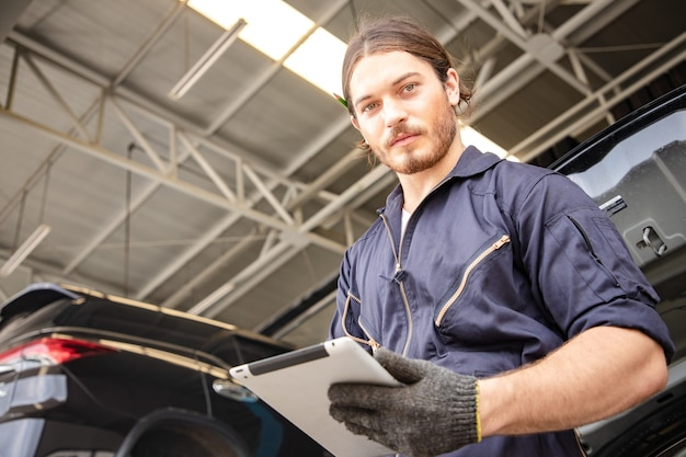 Handsome man mechanics in uniform is working in auto service with lifted vehicle and tablet. Premium Photo