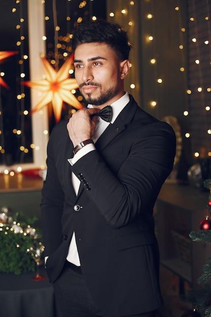 Красивый мужчина возле елки. джентельман в черном костюме. Бесплатные Фотографии