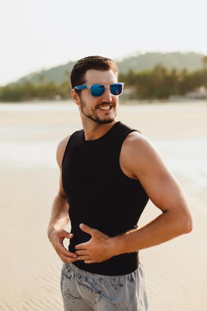 Ritratto di uomo bello all'aperto, in spiaggia. indossare maglietta e pantaloncini neri senza maniche. tempo caldo sole vicino al mare Foto Gratuite