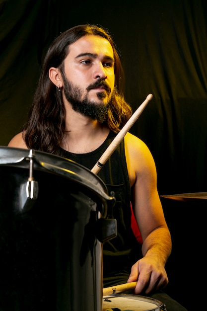 Handsome man playing drums with sticks Free Photo
