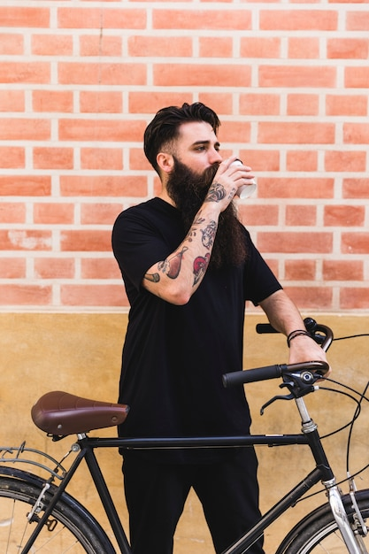 Handsome man posing near his cycle against wall Free Photo