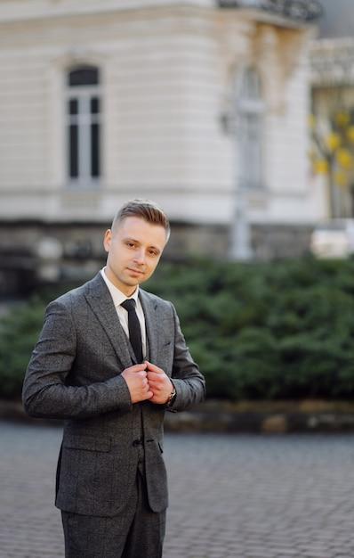 Uomo bello che posa in abito da sposa per le strade Foto Gratuite