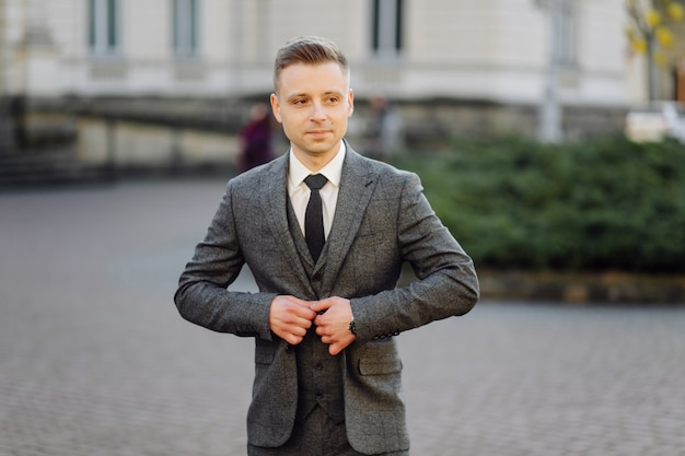 Handsome man posing in wedding suit in the streets Free Photo