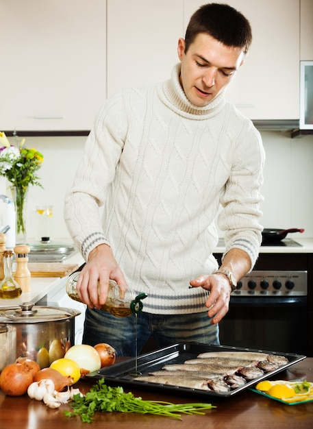 Handsome man pouring oil in raw fish on roasting pan Free Photo