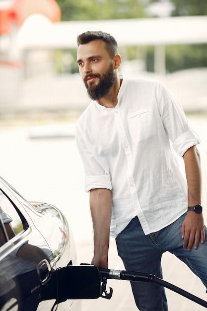 L'uomo bello versa la benzina nel serbatoio dell'automobile Foto Gratuite