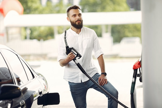 Handsome man pours gasoline into tank of car Free Photo