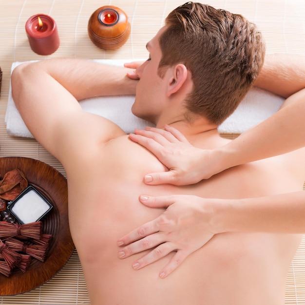 Красивый мужчина расслабился и наслаждается массажем спины глубоких тканей в спа-салоне. Бесплатные Фотографии