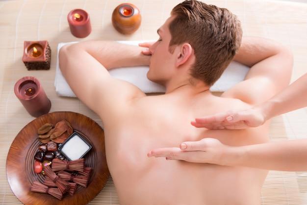 Uomo bello rilassato e godendo di un massaggio alla schiena del tessuto profondo presso il salone spa. Foto Gratuite