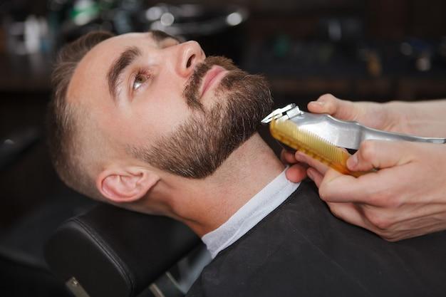 Красивый мужчина расслабился в парикмахерской Premium Фотографии
