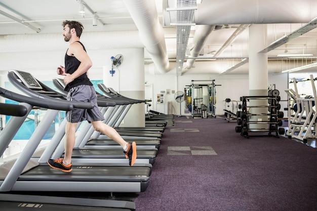 Handsome man running on treadmill Premium Photo
