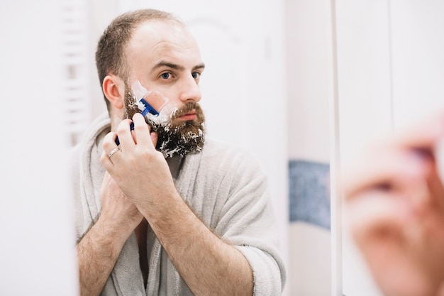 Handsome man shaving in morning Free Photo