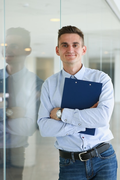 Handsome man in shirt and folder stand in office looking in camera hands crossed on chest. white collar dress codemodern office lifestyle graduate college study profession idea coach train concept Premium Photo