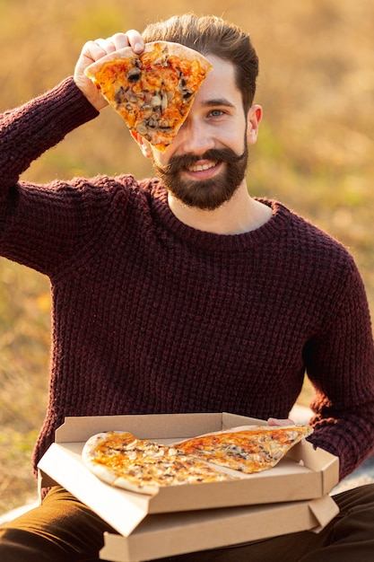 Handsome man showing a slice of pizza Free Photo