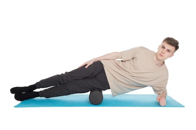 Handsome man shows exercises using a foam roller Premium Photo