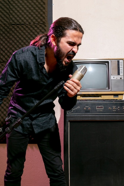 Handsome man singing on microphone Free Photo