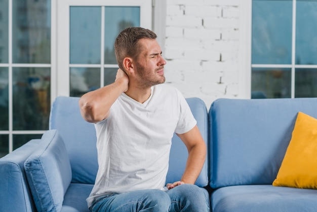 Handsome man sitting on cozy sofa suffering from painful neck Free Photo