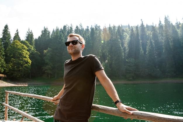 Uomo bello che sorride, godendo della vista delle montagne, del lago e della foresta Foto Gratuite