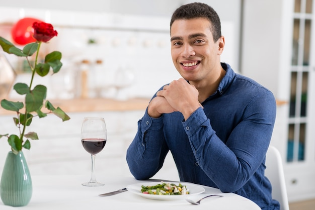 Handsome man smiling while sitting at the table Free Photo