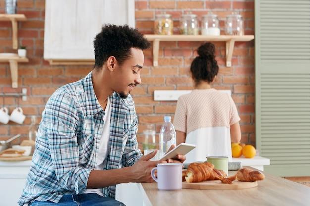 Красивый мужчина проводит утро на кухне, завтракает, читает электронную книгу или тексты с друзьями с помощью цифрового планшета Бесплатные Фотографии