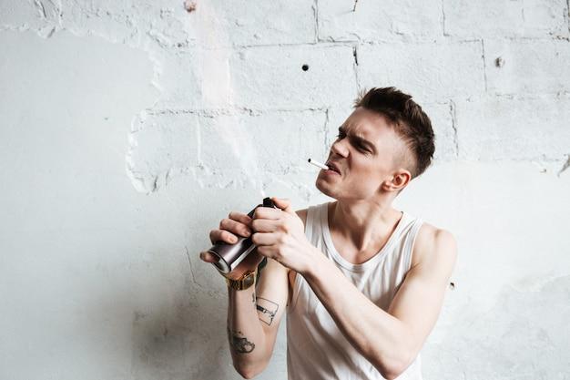 Uomo bello che sta sul pavimento con lo spruzzo e la sigaretta di gas Foto Gratuite