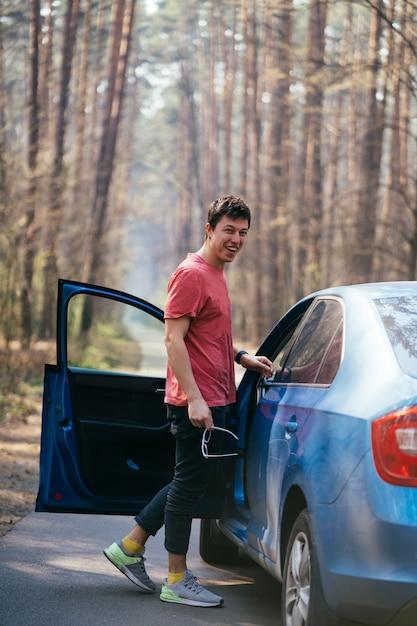 Красивый мужчина стоял на дороге возле открытой двери своего автомобиля. Бесплатные Фотографии