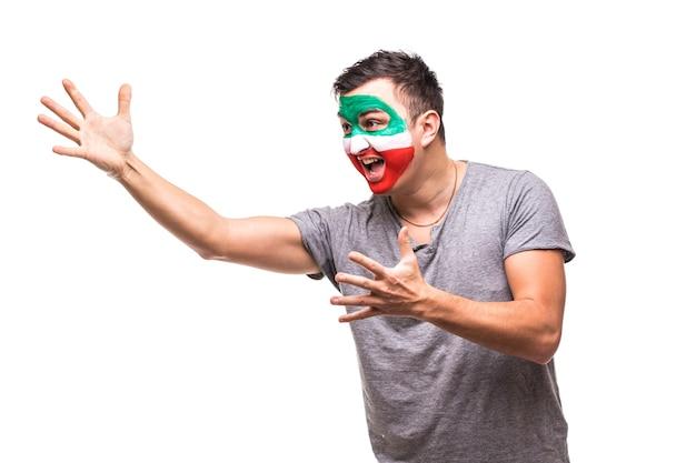 Красивый мужчина, сторонник национальной сборной ирана, нарисовал лицо флага и радуется победе, крича, указывая рукой. поклонники эмоций. Бесплатные Фотографии
