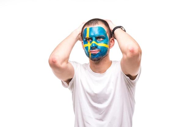 스웨덴 대표팀 그려진 깃발 얼굴의 잘 생긴 남자 후원자 팬은 카메라에 불행한 슬픈 좌절 감정을 얻습니다. 팬들의 감정. 무료 사진