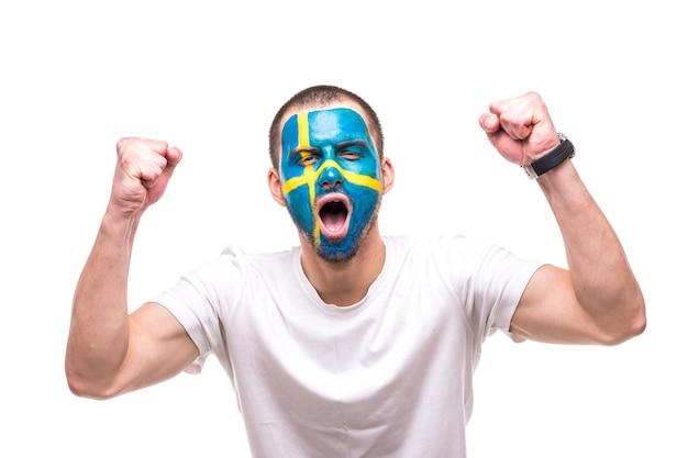 그려진 깃발 얼굴로 스웨덴 국가 대표팀의 잘 생긴 남자 팬 팬은 카메라에 비명을 지르는 행복한 승리를 얻습니다. 팬들의 감정. 무료 사진