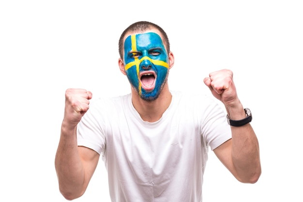 Handsome man supporter fan of sweden national team with painted flag face get happy victory screaming into a camera. fans emotions. Free Photo
