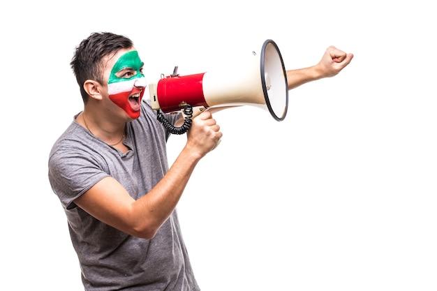Красивый мужчина, сторонник и верный болельщик национальной сборной ирана с раскрашенным флагом, радуется победе, крича в мегафон острой рукой. поклонники эмоций. Бесплатные Фотографии