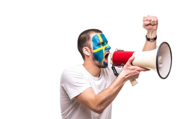 그려진 깃발 얼굴을 가진 스웨덴 국가 대표팀의 잘 생긴 남자 팬 충성스러운 팬은 뾰족한 손으로 확성기로 비명을 지르는 행복 승리를 얻습니다. 팬들의 감정. 무료 사진