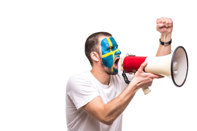 Handsome man supporter loyal fan of sweden national team with painted flag face get happy victory screaming into megaphone with pointed hand. fans emotions. Free Photo