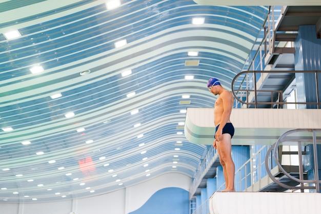 Handsome man swimmer preparing to jump Free Photo