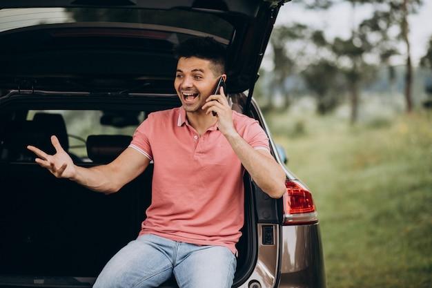 Красивый мужчина разговаривает по телефону на машине Бесплатные Фотографии