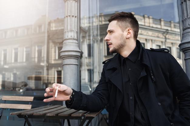 Uomo bello in nero totale con sigaretta, guardando lontano. Foto Gratuite