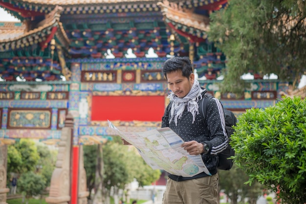 Handsome man tourism, traveler with camera, maps, backpack and tripod,chinese architecture background at yunnan province, china Premium Photo