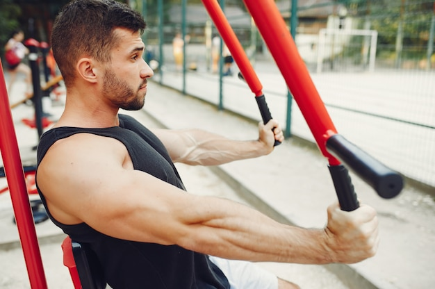 Handsome man training in a summer park Free Photo