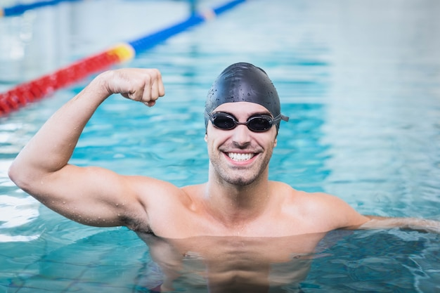 Handsome man triumphing with raised arms in the pool Premium Photo
