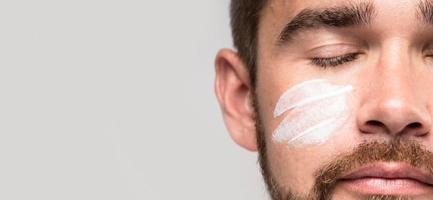 Красивый мужчина с закрытыми глазами, используя крем для лица Бесплатные Фотографии