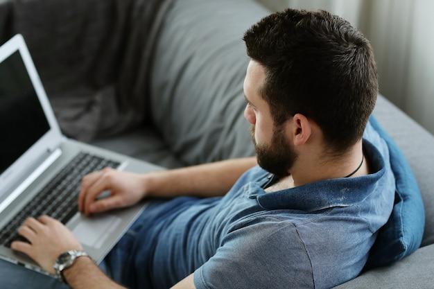 自宅でラップトップを使用してハンサムな男。在宅勤務のコンセプト 無料写真