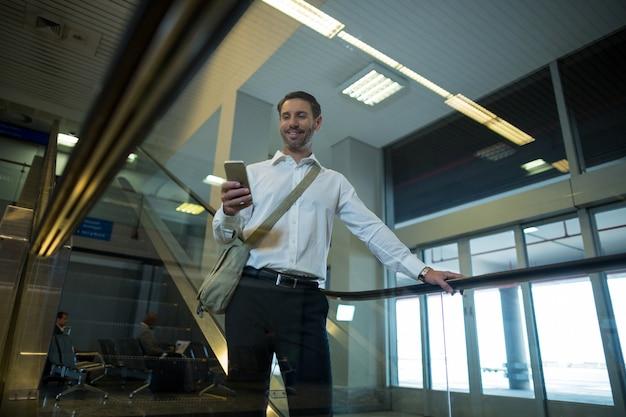 Красивый мужчина с помощью мобильного телефона на эскалаторе Бесплатные Фотографии