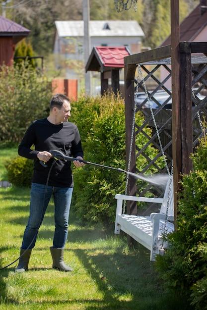 Красивый мужчина моет деревянные качели мойкой высокого давления Premium Фотографии