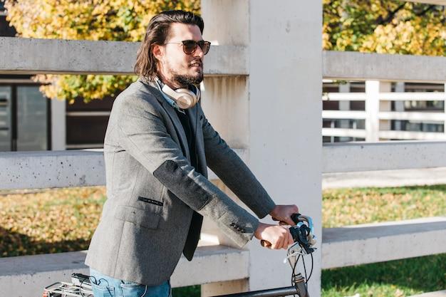 Красивый мужчина в темных очках езда на велосипеде Бесплатные Фотографии