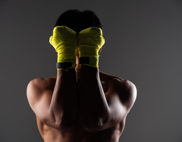 The handsome man wearing yellow mitt, put hands to closed  his face, show fist, prepare for punching Premium Photo