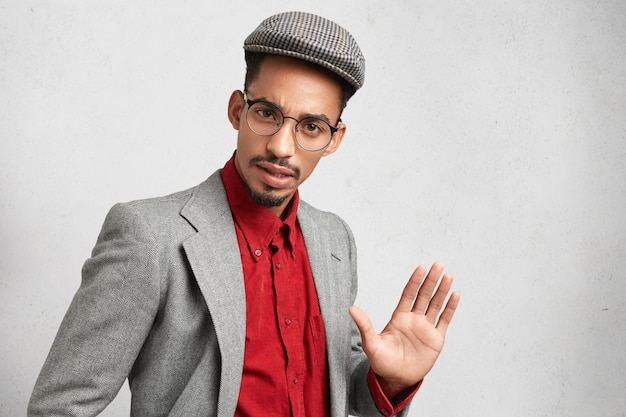 Handsome man wears round spectacles, wears old fashioned clothes, shows palm, tries to stop something Free Photo